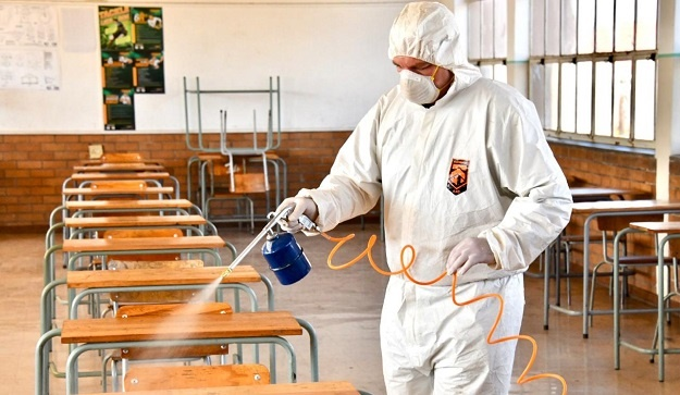 A worker sanitises a classroom.