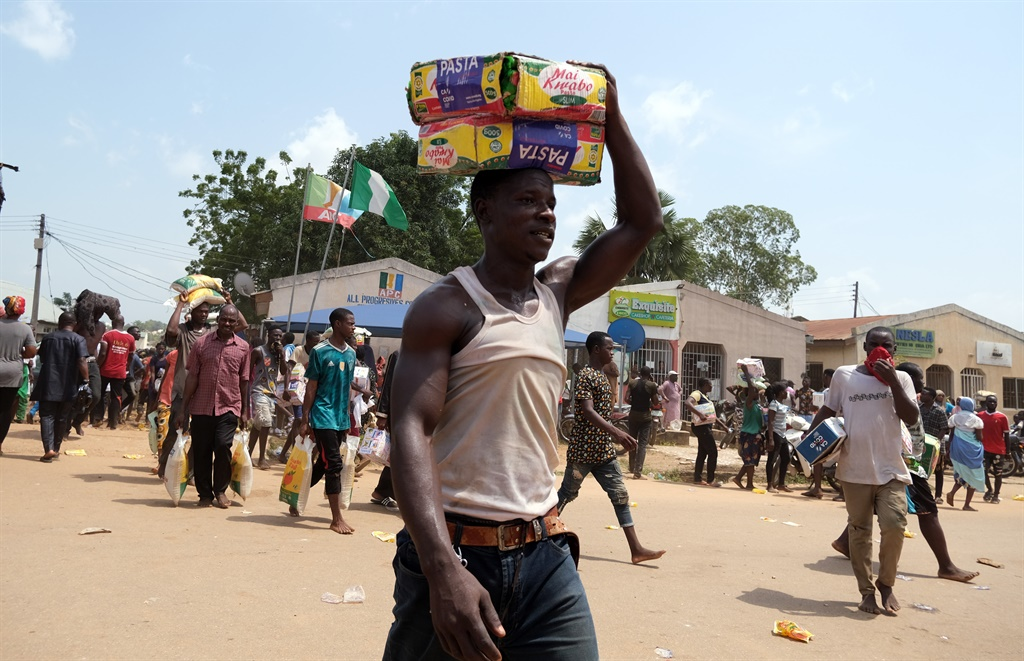 People carry bags of food on their heads during a mass looting of a warehouse that have Covd-19 food palliatives that were not given during lockdown to relieve people of hunger, in Abuja, Nigeria, on 26 October, 2020.