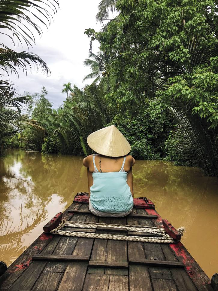 The canals of the Mekong Delta are surrounded by lush palm forests.