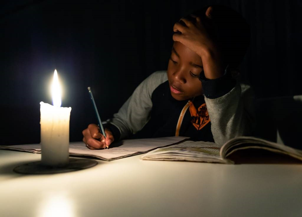 A young Zimbabwean boy does his homeworks under a