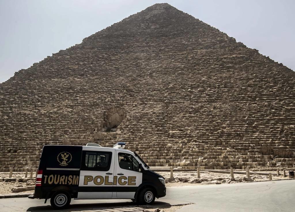 An Egyptian police car patrols the Giza pyramids necropolis.