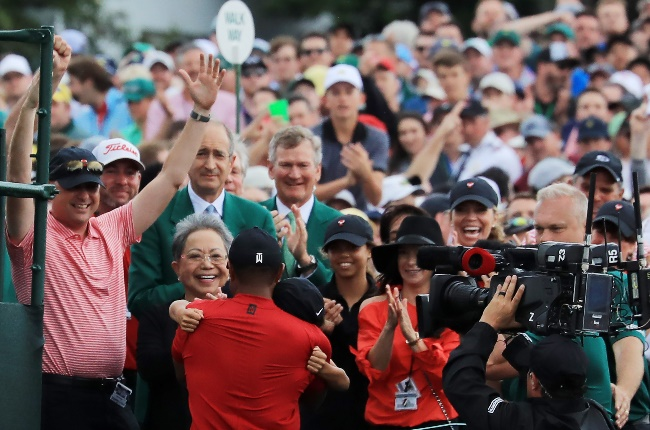 Tiger Woods wraps his arms around his son after wi
