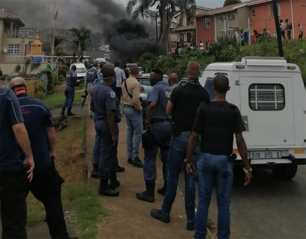 Police look on as two decapitated bodies burn in Shallcross.