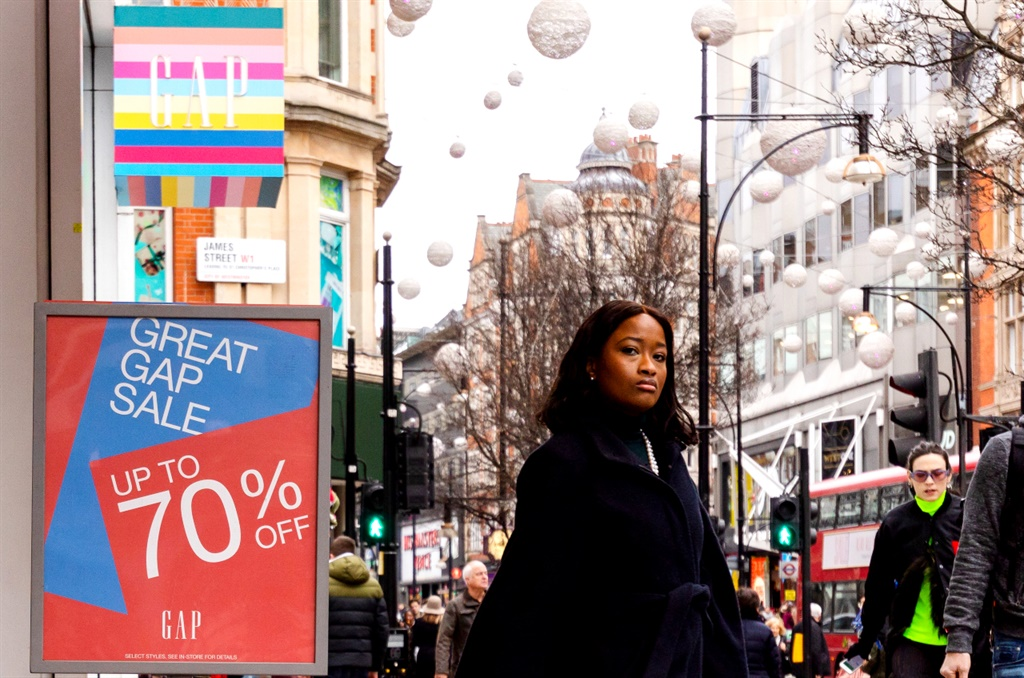 A woman walks past a 70% sale sign outside a branch of Gap in Oxford Street, London. (Photo by Vickie Flores/In Pictures via Getty Images Images)