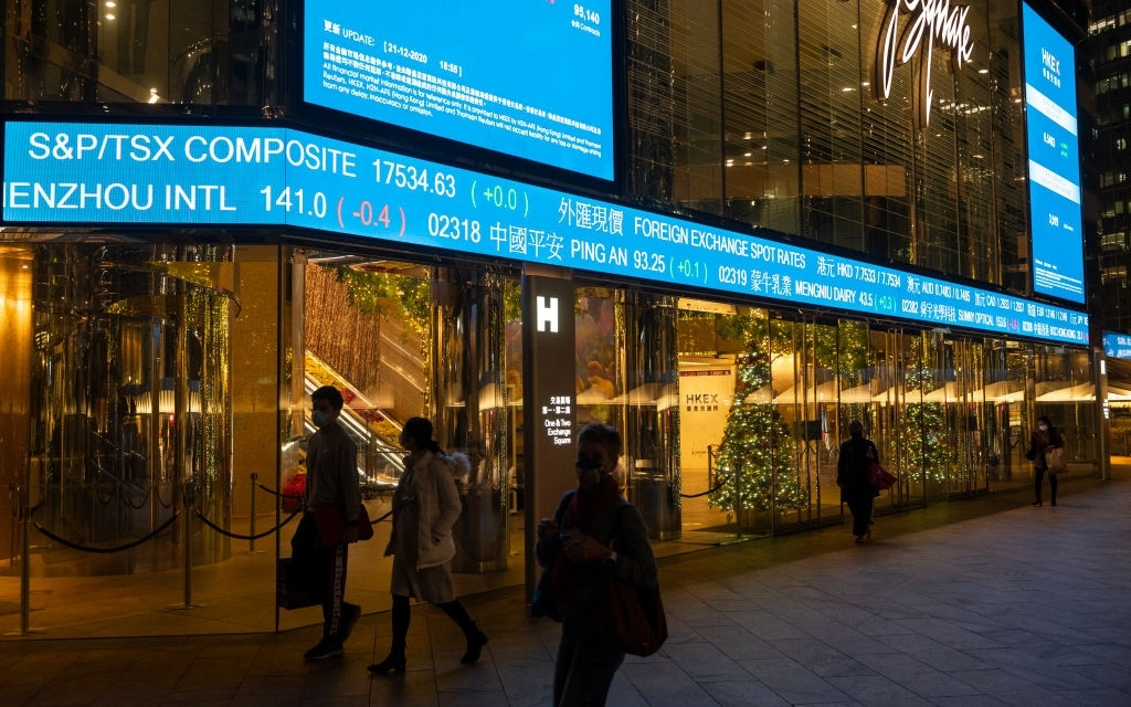 Pedestrians walk past a stock market display board showing the losses at Hang Seng Index results in Hong Kong.