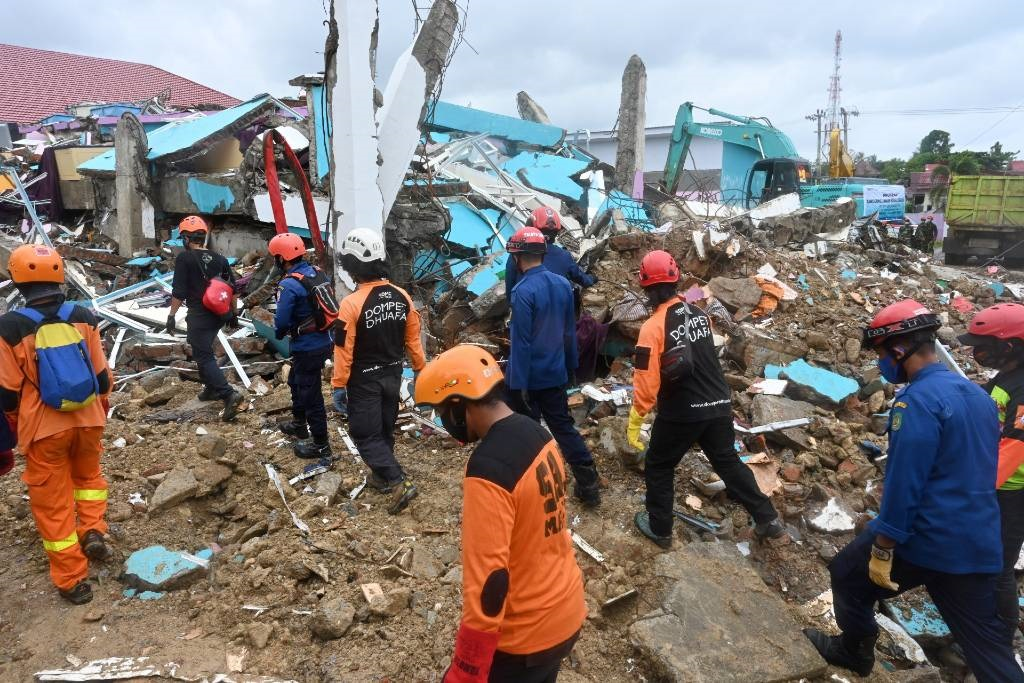 Rescue teams look for people trapped in rubble