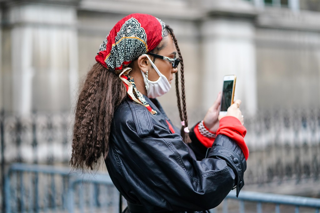 A guest wears a red bandanna, a white face mask, a black leather jacket, outside Yohji Yamamoto, during Paris Fashion Week - Womenswear Spring Summer 2021, on October 02, 2020 in Paris, France. Photo by Edward Berthelot/ Getty Images