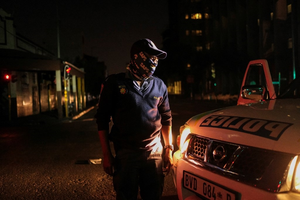 A South African Police Service officer stands next to his vehicle as they patrol the street after the new lockdown curfew, to help curb the spread of Covid-19, in Johannesburg.
