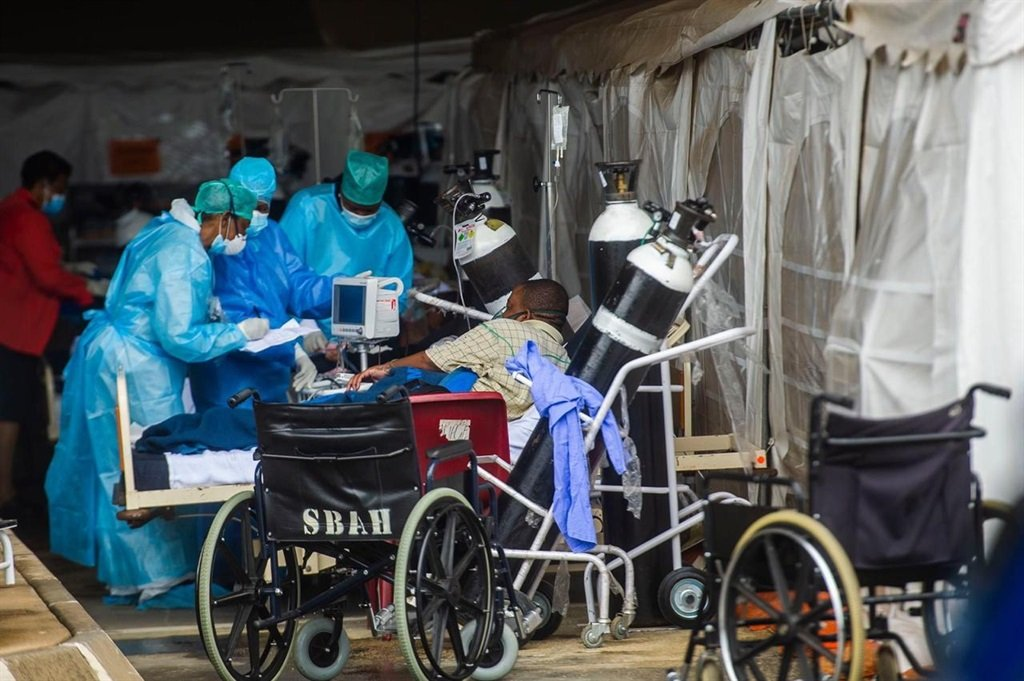 Healthcare workers and patients in the temporary area outside Steve Biko Academic Hospital, created to screen and treat suspected Covid-19 cases.