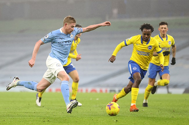 Kevin De Bruyne of Manchester City shoots under pressure from Percy Tau of Brighton and Hove Albion during the Premier League match between Manchester City and Brighton & Hove Albion at Etihad Stadium on January 13, 2021 in Manchester, England. Sporting stadiums around England remain under strict restrictions due to the Coronavirus Pandemic as Government social distancing laws prohibit fans inside venues resulting in games being played behind closed doors.