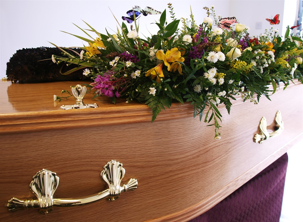 A coffin decorated with flowers awaits collection from the undertakers . (Image: Getty)