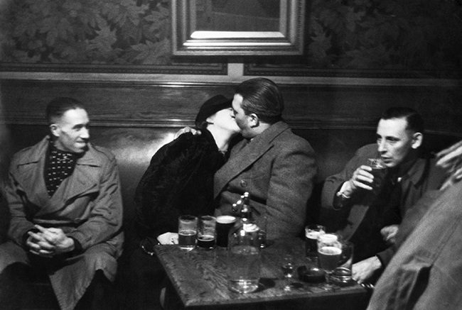 A couple shares a kiss over drinks. (Photo by Hulton-Deutsch/Hulton-Deutsch Collection/Corbis via Getty Images)