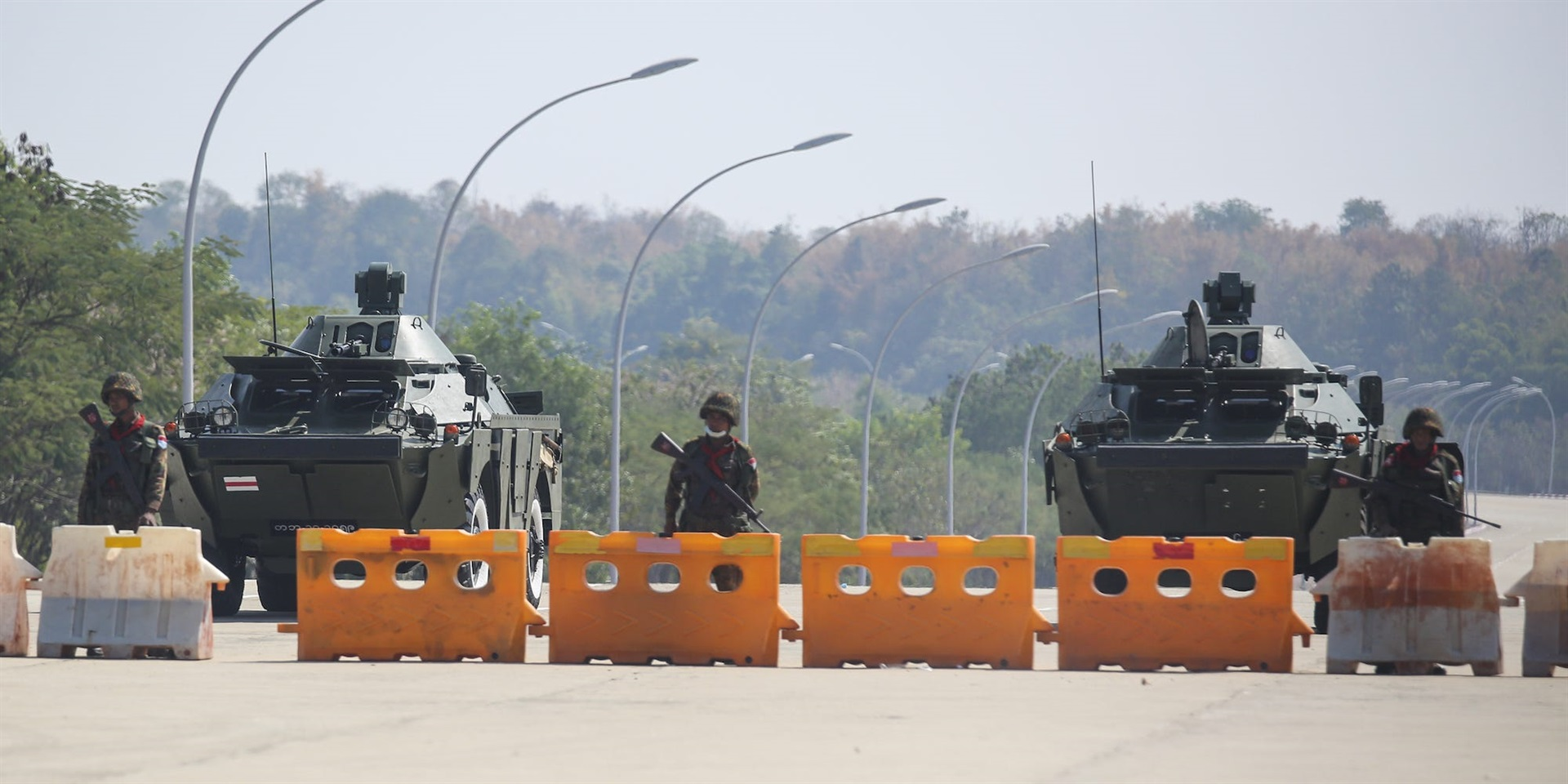 Troops with armored vehicles block the road near Parliament in Naypyidaw in Myanmar on Monday.