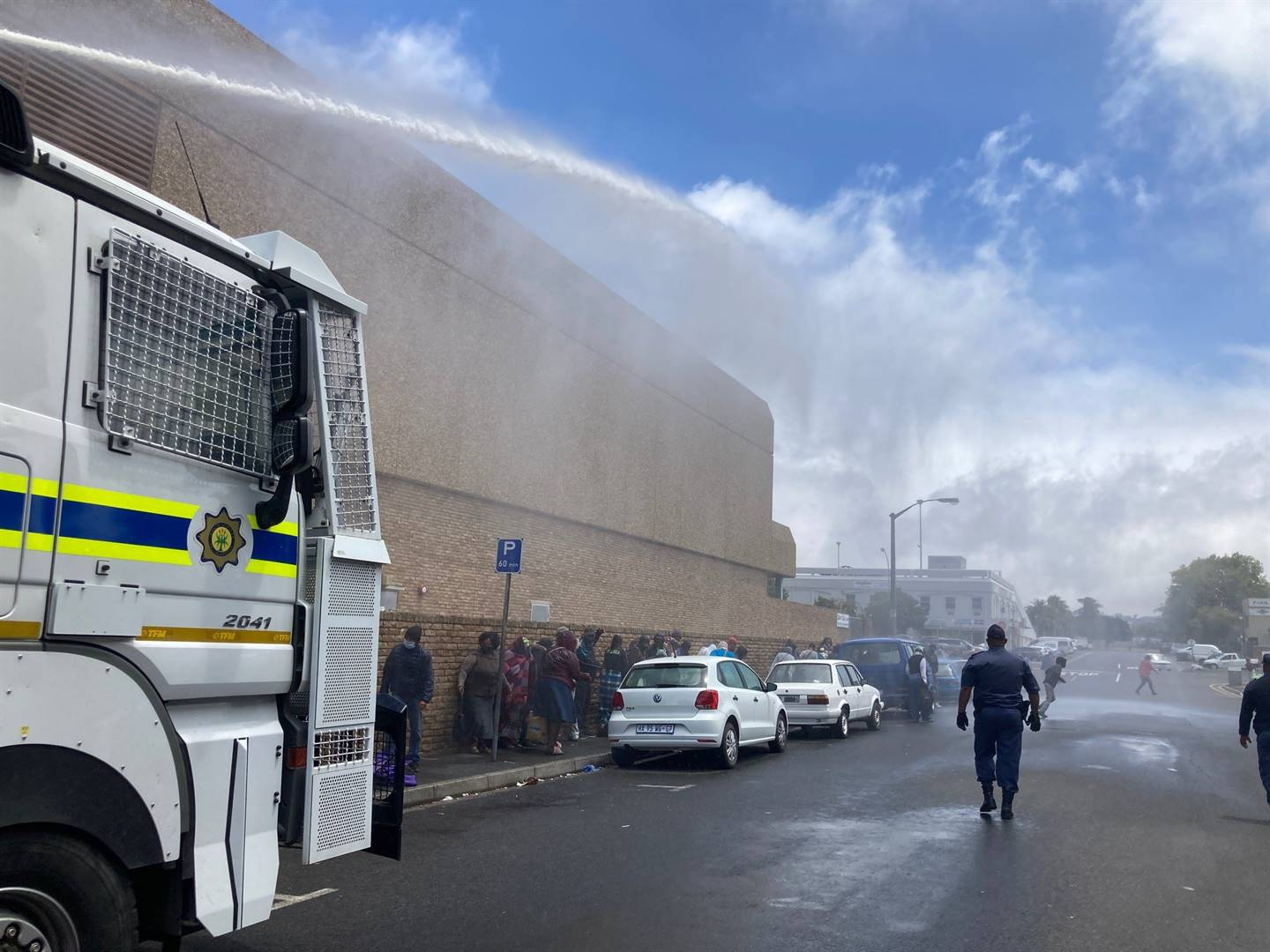 Police fire a water cannon at queueing beneficiaries outside Sassa's offices in Bellville.
