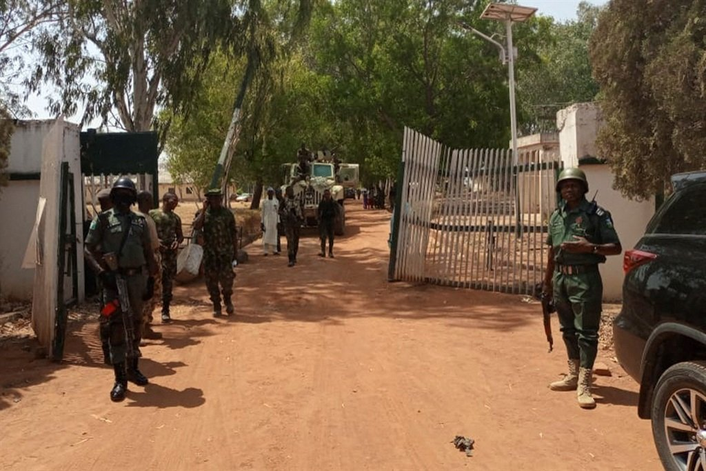 Nigerian soldiers and police officers stand at the entrance of the Federal College of Forestry Mechanization in Mando, Kaduna state, on 12 March, 2021, after a kidnap gang stormed the school shooting indiscriminately before taking at least 30 students.