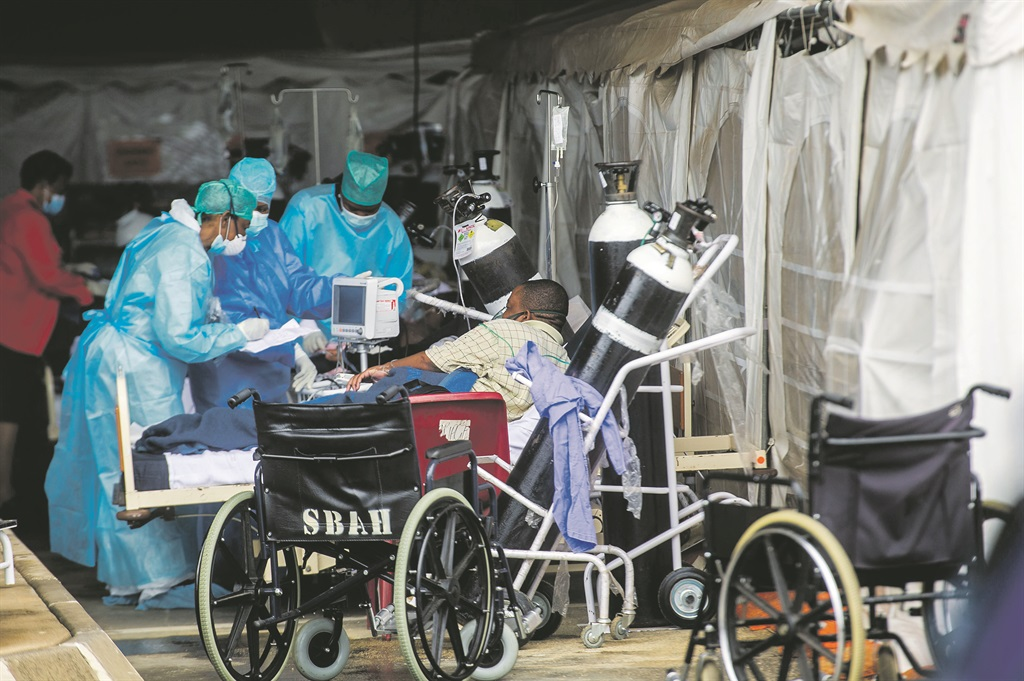 Healthcare workers take care of patients in a temporary structure outside Steve Biko Academic Hospital in Pretoria earlier this year. The structure was erected when the hospital ran out of space for patients. Picture: Alet Pretorius / Gallo Images