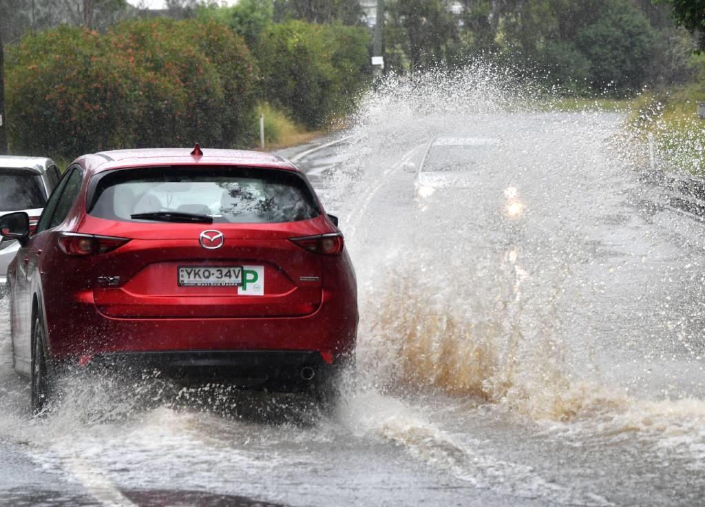 Motorists commute along a flooded road near Warrag
