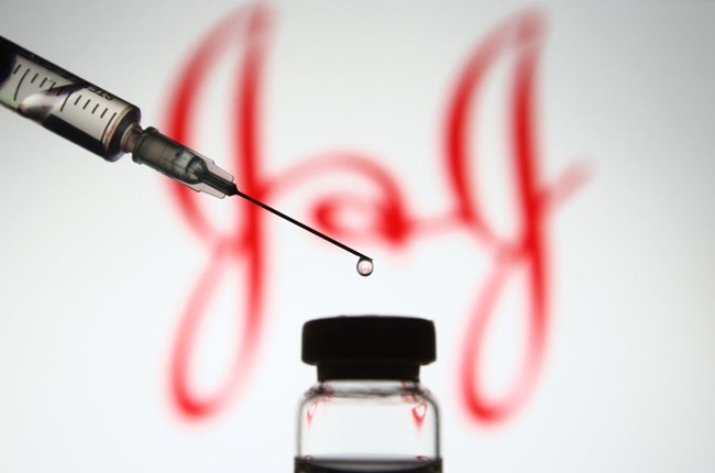 The Johnson & Johnson logo appears in front of a medical syringe and a vial containing a coronavirus vaccine.