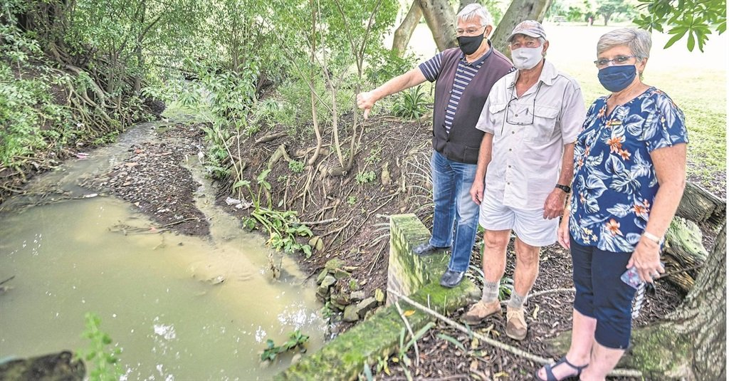 Councillor Vic Winterbach with the former Pelham headmaster Louis Botha and the school's current principal, Lorrel Wissing, at the polluted sewage-laden stream that runs through Pelham Park.