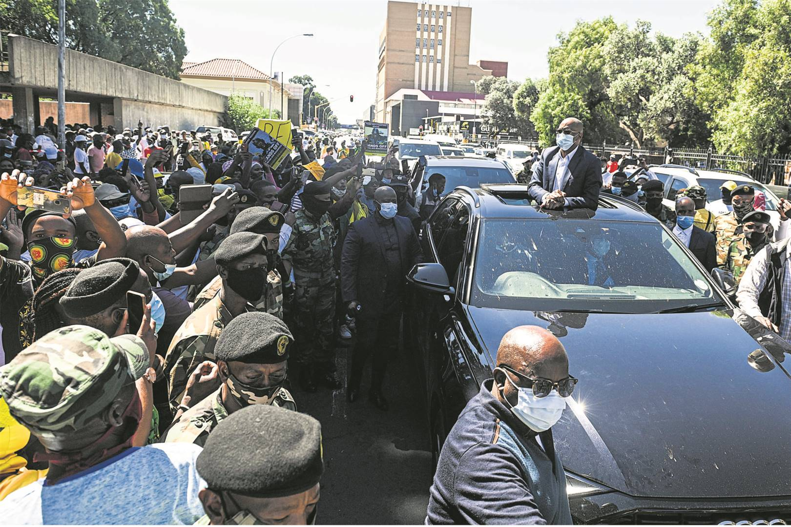 ANC secretary-general Ace Magashule, being driven in a luxury car, salutes his supporters shortly after reappearing in the Bloemfontein Magistrate's Court on 19 February 2021.