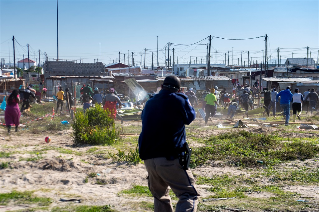 Members of the Metro Police clash with angry members of the Khayelitsha community over land invasions on July 21, 2020 after the City's Anti-Land Invasion Unit, accompanied by law enforcement officers demolished informal structures at eThembeni near Empolweni in Khayelitsha