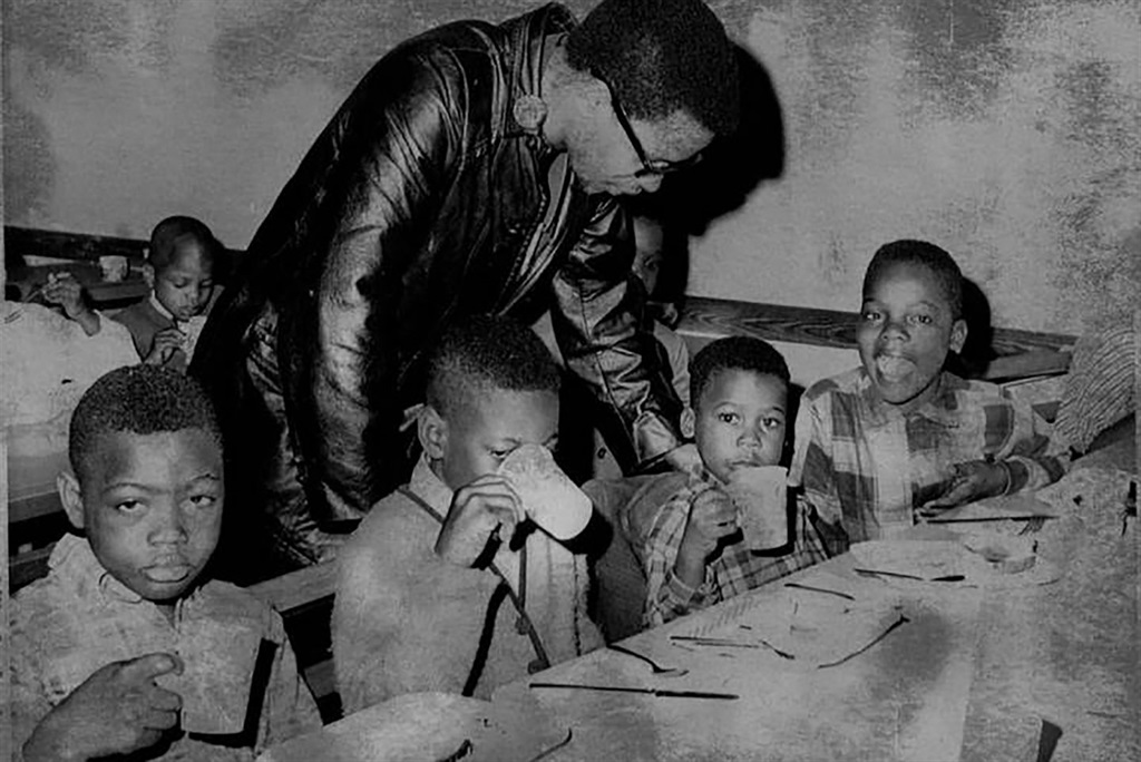 1969: Pete O'Neal chats with children eating a fre