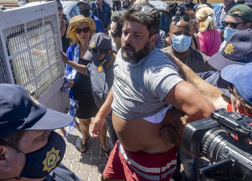 Craig Peiser is confronted by members of the media after his arrest following an incident between him and eNCA journalist Monique Mortlock during a protest at the Fish Hoek Beach.