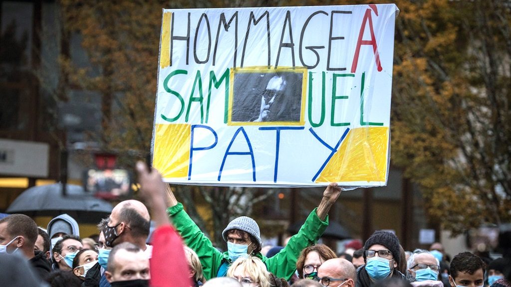 Locals pay tribute to Samuel Paty outside the school where he taught, in the Paris suburb of Conflans-Sainte-Honorine, on 20 October 2020.