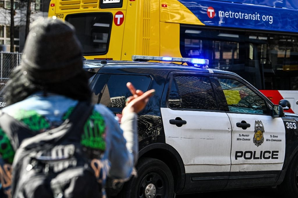 A protester flips off a police car outside the Hennepin County Government Center on 8 March 2021, after the first day of jury selection began in the trial of former Minneapolis police officer Derek Chauvin who is accused of killing George Floyd.