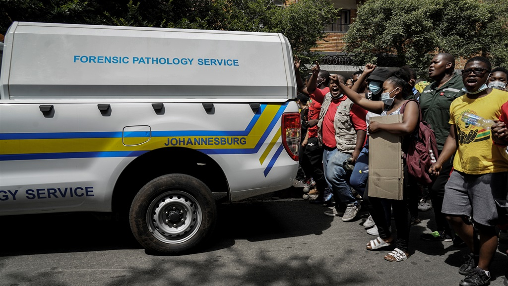 Students march behind a forensics vehicle carrying