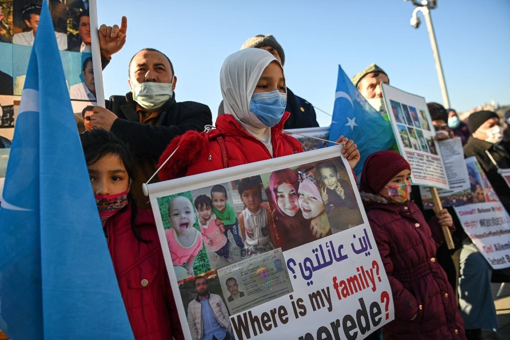 Members of the Uighur minority community hold placards as they demonstrate to ask for news of their relatives and to express their concern about the ratification of an extradition treaty between China and Turkey, on 22 February 2021.