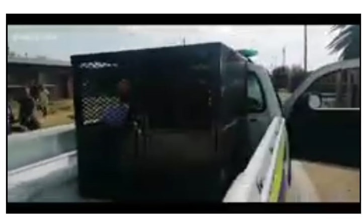 In a video shared on social media a man can be seen handcuffed in a police dog cage.