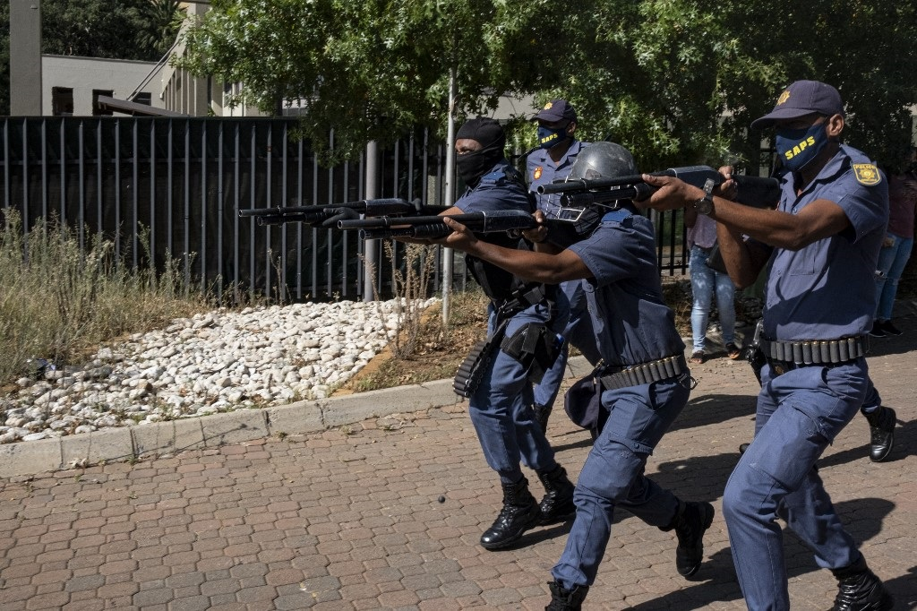 A large group of police officers disperse a group of Wits students.