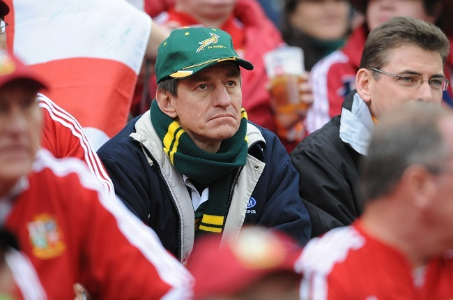 A Springbok fan sits between a legion of Lions supporters. (Gallo Images)