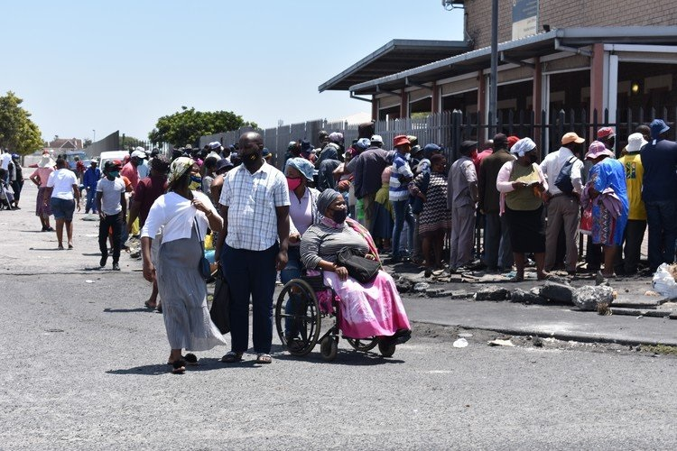 Hundreds of people are queueing outside the gates of the Sassa office in Gugulethu, Cape Town, trying to renew their lapsed disability grants on Tuesday. (Photo: Buziwe Nocuze, GroundUp)