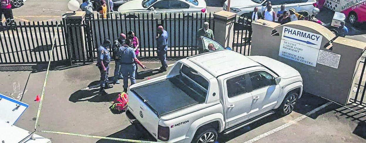 Police and paramedics cordon off the Duzimed Medical Centre parking area yesterday after two men were gunned down. PHOTO: Netcare911