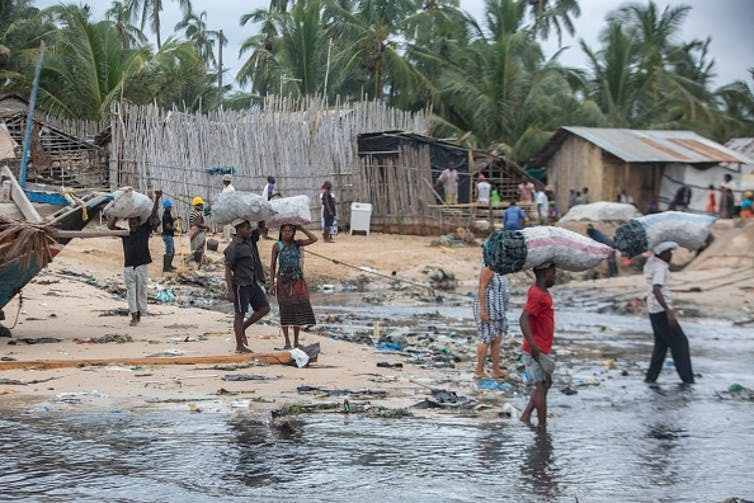 People displaced by the atacks on the town of Palma, northern Mozambique, flee to safety with meagre possessions. (Alfredo Zuniga / AFP via Getty Images)