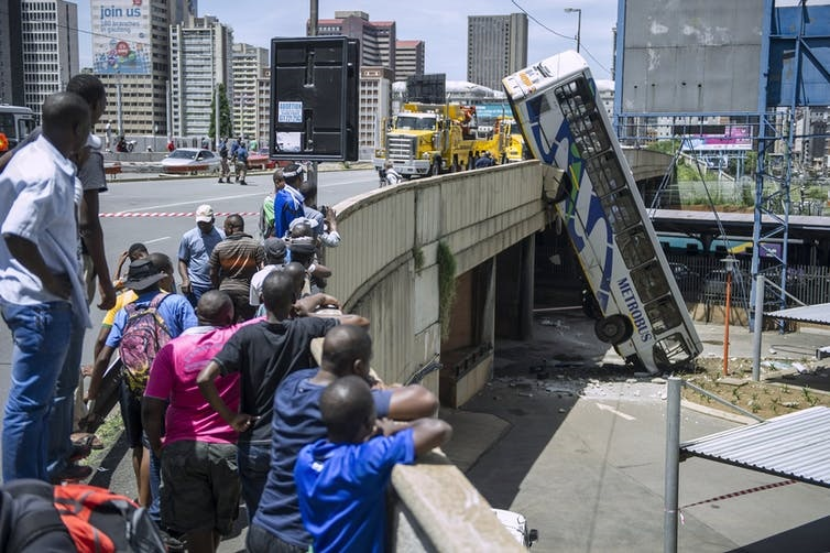 Onlookers gather on Queen Elizabeth bridge to look at a public transport bus that drove over the side of the bridge in Johannesburg, South Africa. (Mujahid Safodien/AFP via Getty Images)