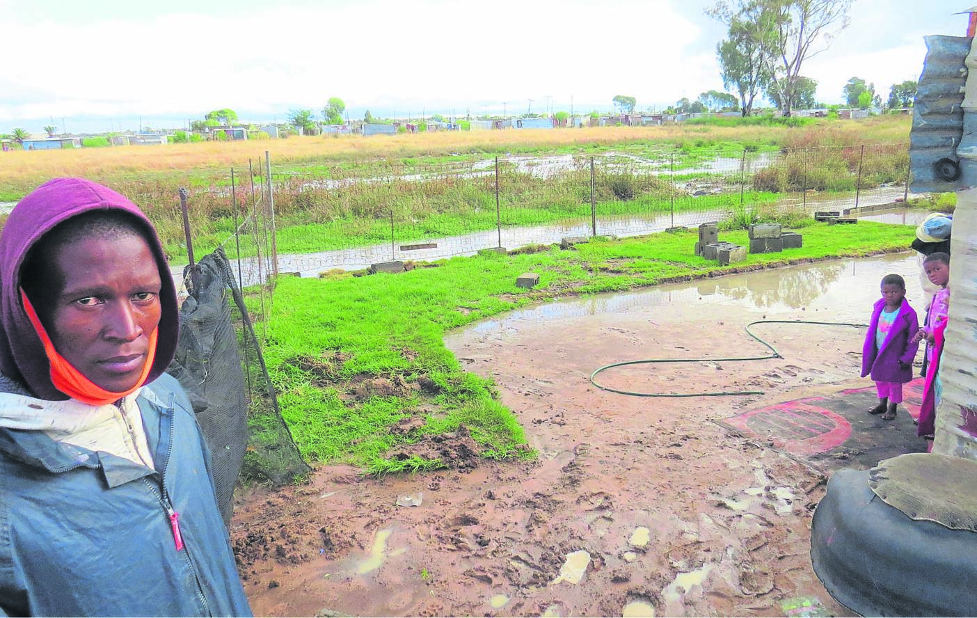 Moses Molantoa outside in the flooded yard in the Khayelitsha settlement in ward 17, Bloemfontein.  Photo: Teboho Setena