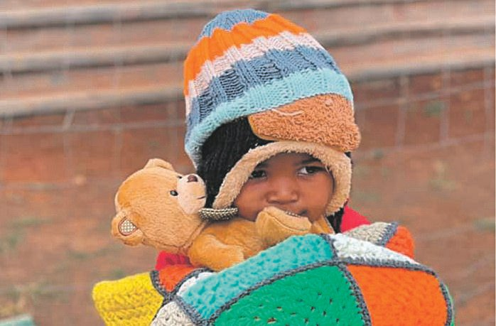 Three-year-old Yamkela Zuma cuddles his teddy while wrapped head to toe in some of the warm woollen goodies donated to Angels' Care Centre in Howick.