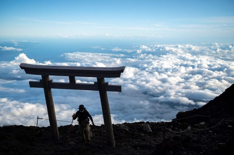 A man reaching the summit of Mount Fuji. Image Cre