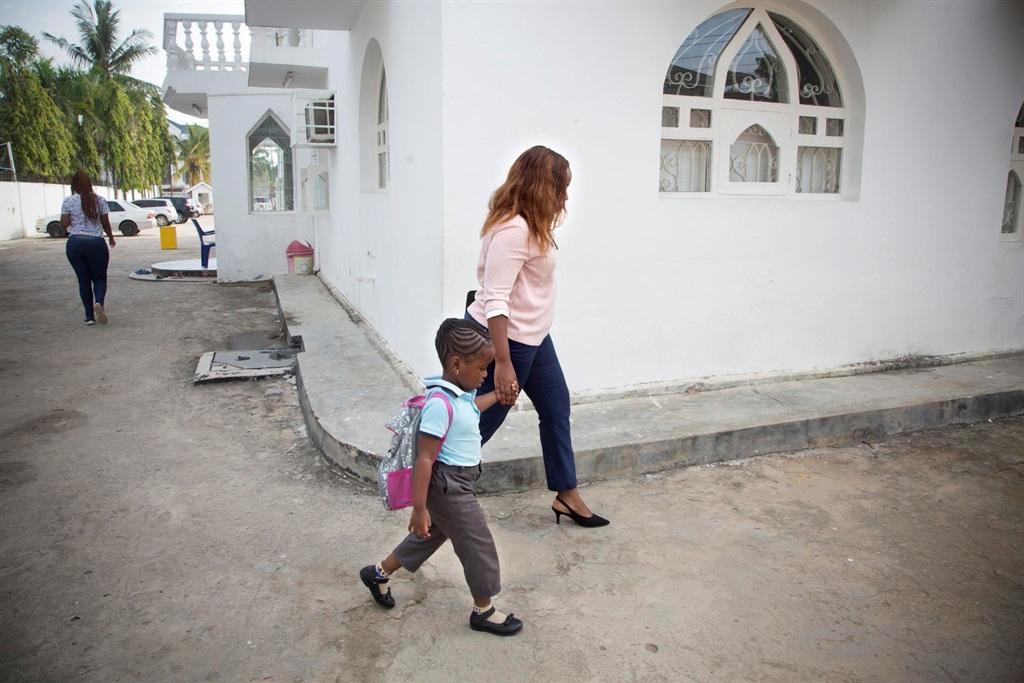 Mother walking daughter to school.