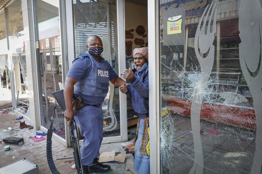 An elderly woman screams as she is arrested by a police member following looting and vandalism at the Lotsoho Mall in Katlehong township, east of Johannesburg.