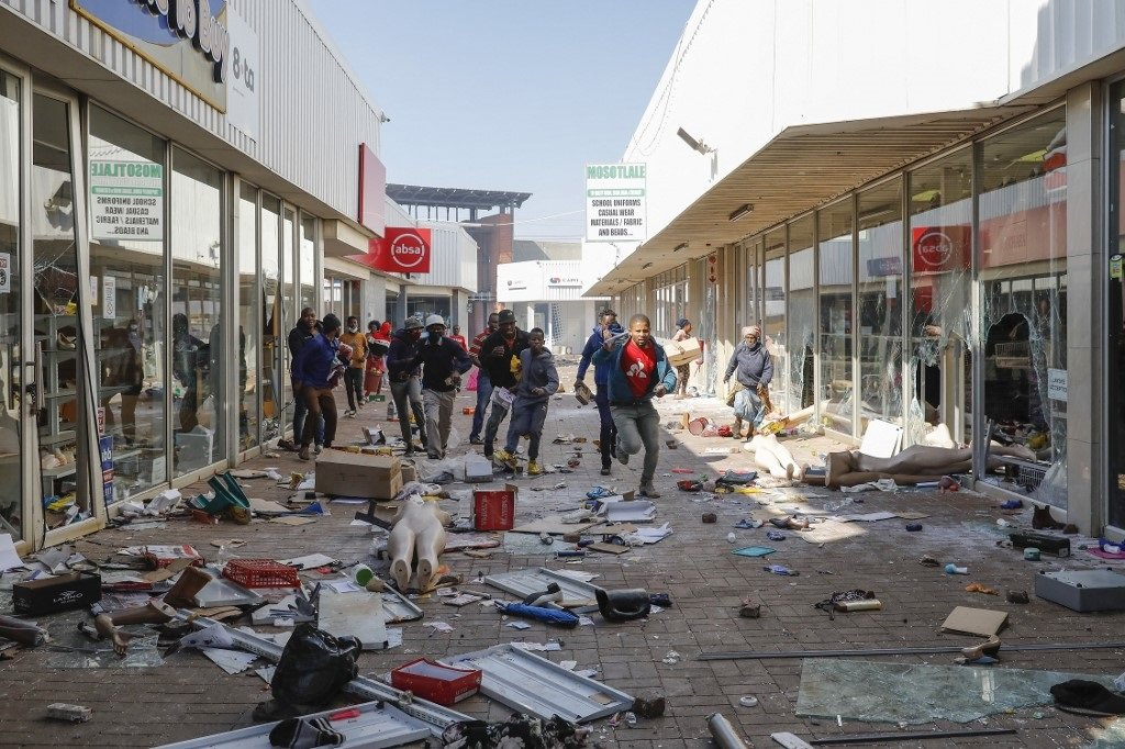 People flee from police as they carry goods while looting and vandalising the Lotsoho Mall in Katlehong township, East of Johannesburg.