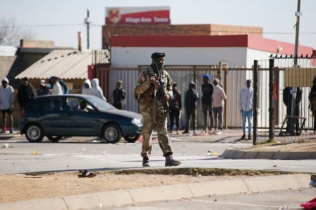 A member of the South African National Defence Force patrols the looted Diepkloof Square area in Soweto, which has been hit by looting.