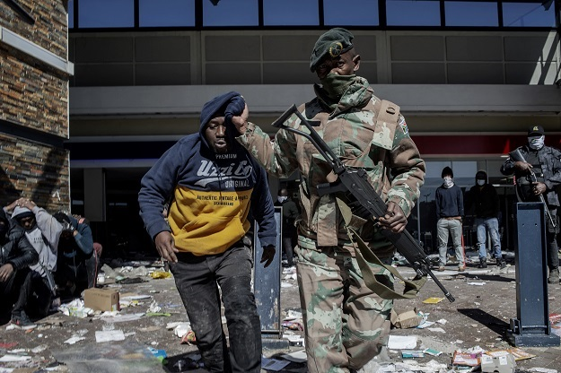 A South Africa National Defence Force soldier detains a suspected looter at Jabulani Mall in Soweto, as rioting continued on Tuesday.