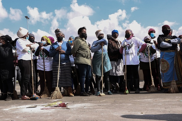 Community members volunteer in a clean up operation in Soweto after days of violent riots affected malls, shops and businesses in the area.