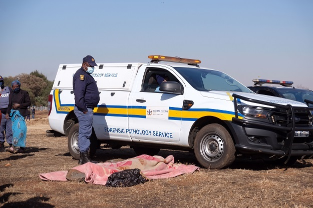 Police and pathology services attend to the body of Vusi Dlamini. Photo: Gallo Images/Dino Lloyd