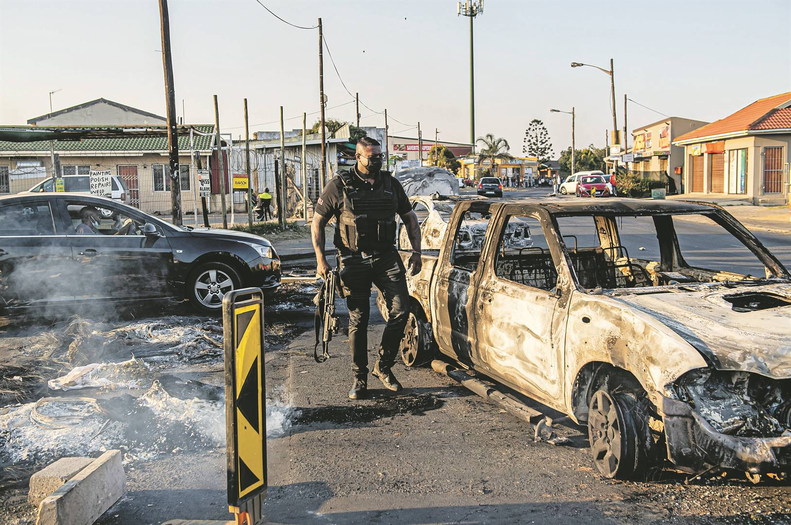 Ashley Deodutt, owner of GBH Security in Phoenix, with a burnt-out car.