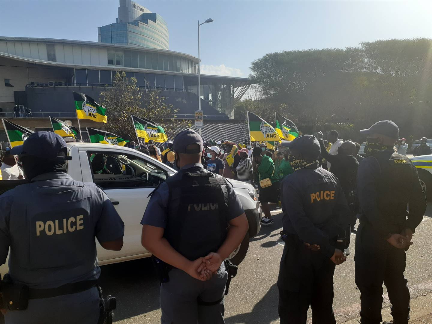 Police watch on as a group of ANC supporters gather outside the ANC provincial offices in Durban.